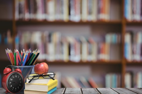 digital composite of School materials and apple with library background