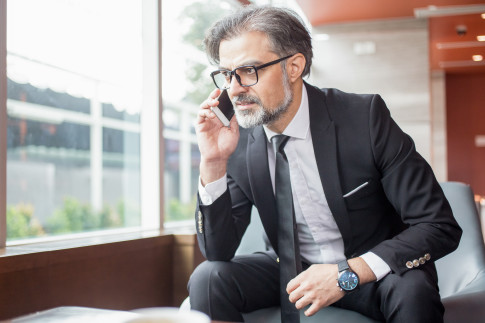 Closeup portrait of tensed middle-aged handsome business man talking on smartphone and sitting in lobby with windows in background
